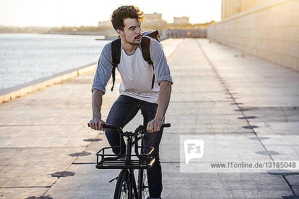Junger Mann mit Rucksack auf dem Fahrrad auf der Uferpromenade am Flussufer