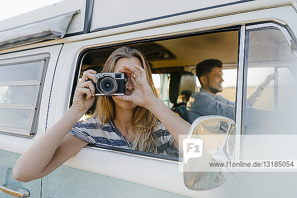 Woman taking picture out of window of a camper van with man driving