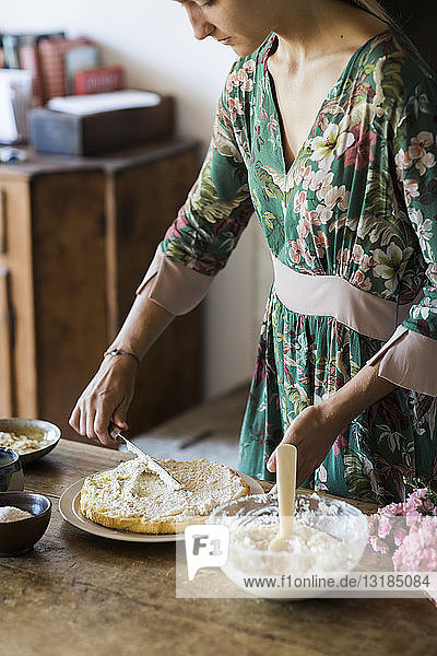 Young woman preparing home-baked cake
