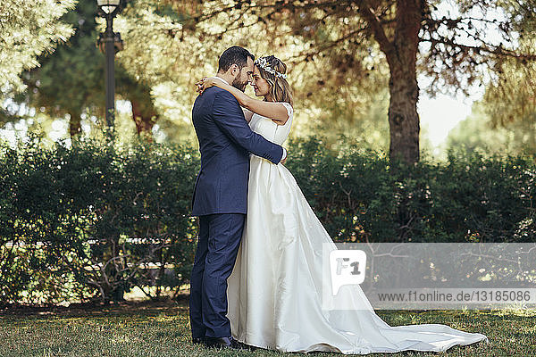 Brautpaar steht Kopf an Kopf mit geschlossenen Augen in einem Park