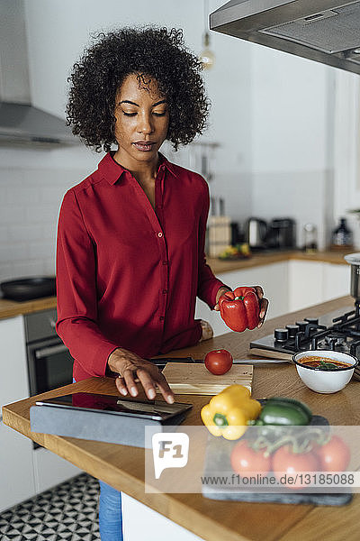 Woman standing in kitchen  chopping vegetables  using digital tablet