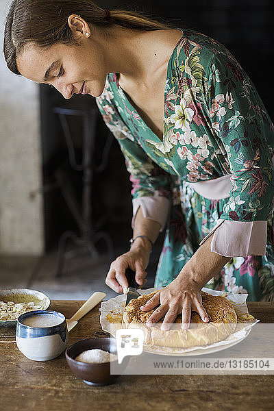 Young woman cutting home-baked cake