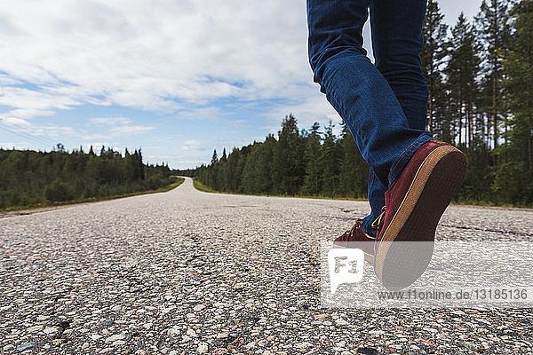 Finnland  Lappland  Menschenfüße auf leerer Landstraße