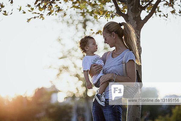 Mother holding her little son outdoors at sunset