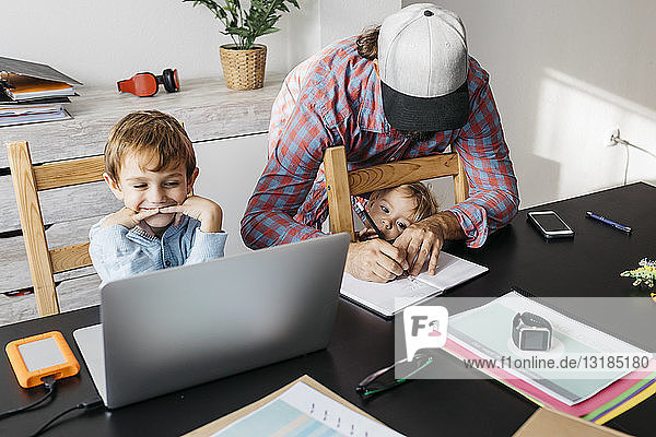 Father writing in notebook while children are playing at his desk