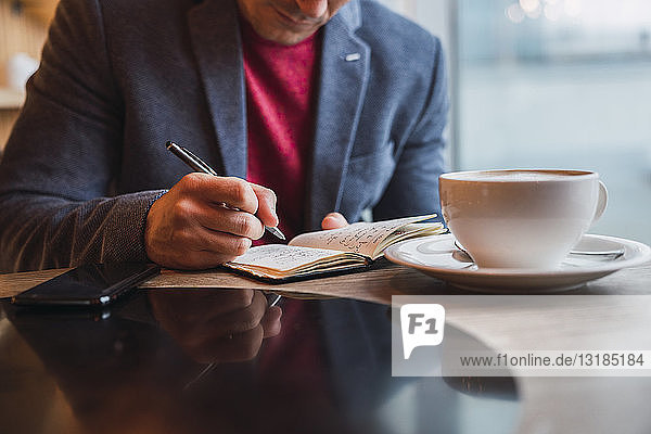 Businessman sitting in restaurant drinking coffee and checking his notebook