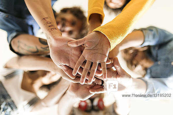 Group of happy friends huddling and stacking hands