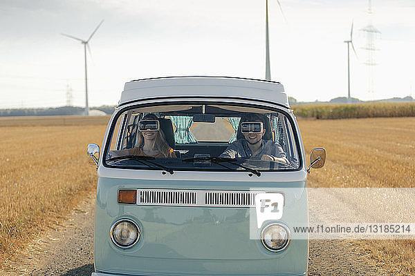 Lächelndes Paar mit VR-Brille fährt Wohnmobil in ländlicher Landschaft