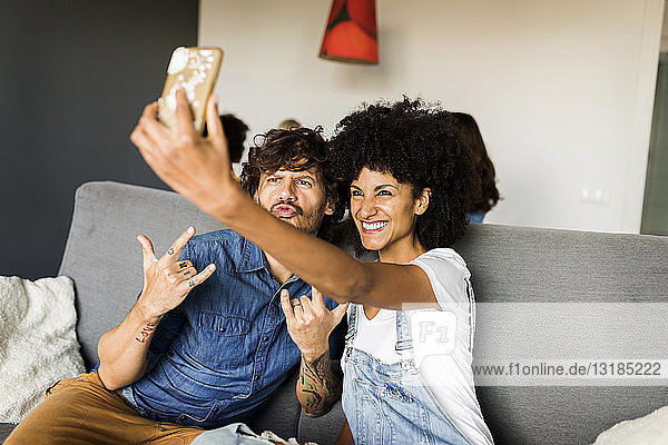 Happy couple sitting on couch taking a selfie