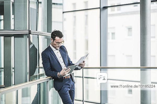 Businessman standing in office building  using digital tablet