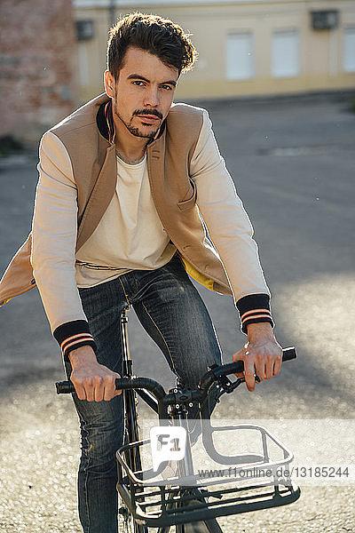 Porträt eines jungen Mannes auf einem Pendler-Fixie-Fahrrad in der Stadt