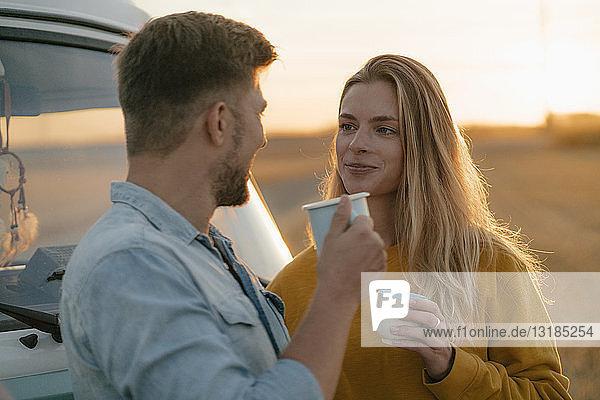 Lächelndes junges Paar hält Becher am Wohnmobil in ländlicher Landschaft