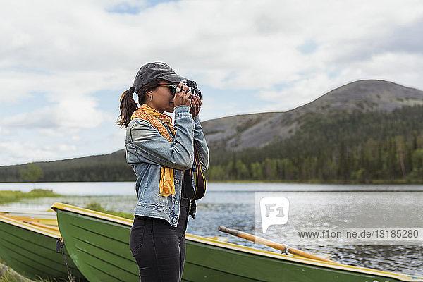 Finnland  Lappland  Frau beim Fotografieren mit einer Kamera am Seeufer