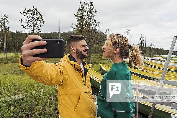 Finnland  Lappland  junges Paar beim lustigen Selbermachen am Seeufer