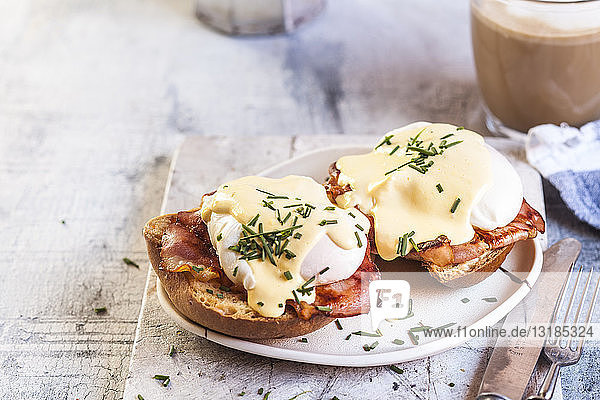 Traditional egg benedict with slices of bacon on toast  poached egg and hollandaise