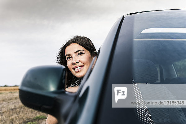Smiling young woman leaning out of car window