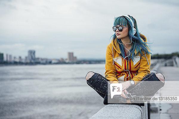 Junge Frau mit blau gefärbten Haaren sitzt an einer Wand und hört mit Kopfhörern und Smartphone Musik
