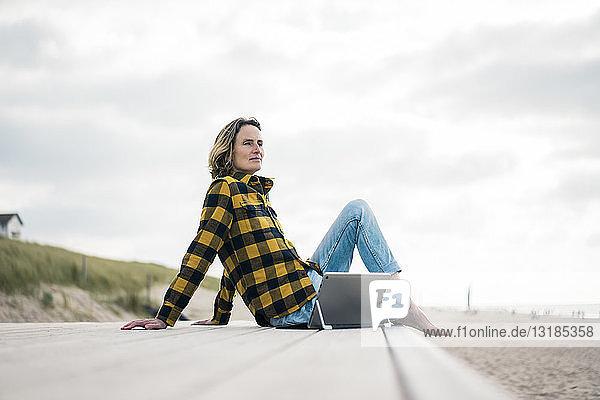Reife Frau sitzt am Strand auf der Strandpromenade und benutzt einen Laptop