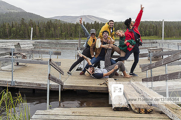 Finnland  Lappland  Porträt glücklicher spielerischer Freunde  die auf einem Steg an einem See posieren