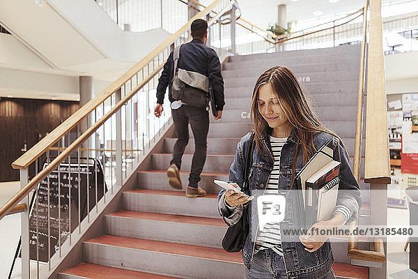 Studentin benutzt Mobiltelefon  während ein Mann eine Treppe in der Universität hinaufgeht