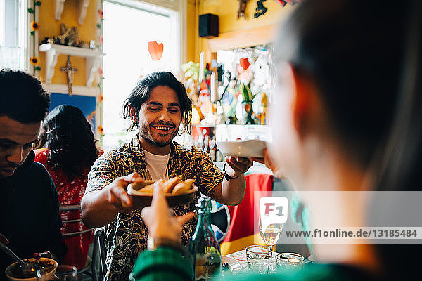 Smiling young man giving food to woman while sitting by friend at table in restaurant during brunch party