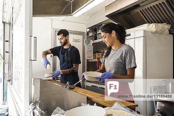 Junge multiethnische männliche und weibliche Kollegen bereiten Essen im Speisewagen zu