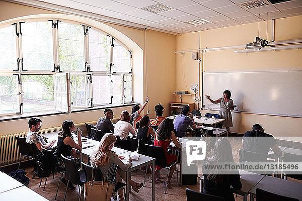 Weibliche Lehrerin stellt Fragen an Schüler in Sprachschule