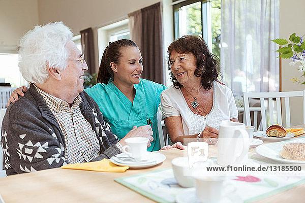 Junge Betreuerin mit älterem Paar beim Frühstück im Pflegeheim
