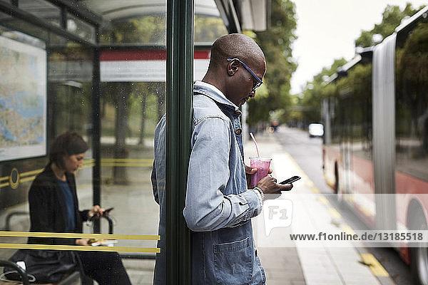 Geschäftsmann benutzt Smartphone  während er ein Getränk an einer Bushaltestelle in der Stadt hält