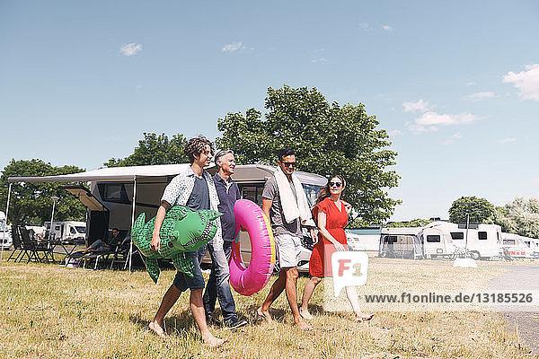 Familie in voller Länge mit aufblasbaren Ringen  die auf einem Grasfeld gegen den Himmel laufen