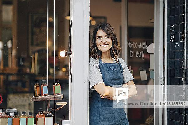 Selbstbewusste Besitzerin schaut weg  während sie am Eingang eines Feinkostladens steht
