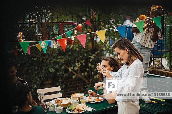Junge Frau fotografiert während der Dinner-Party per Handy