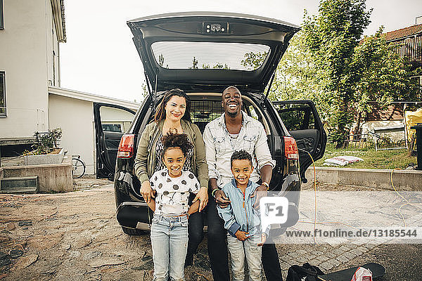 Portrait of smiling multi-ethnic family leaning on car trunk in front yard