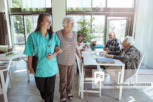 Young nurse and senior woman walking arm in arm at nursing home