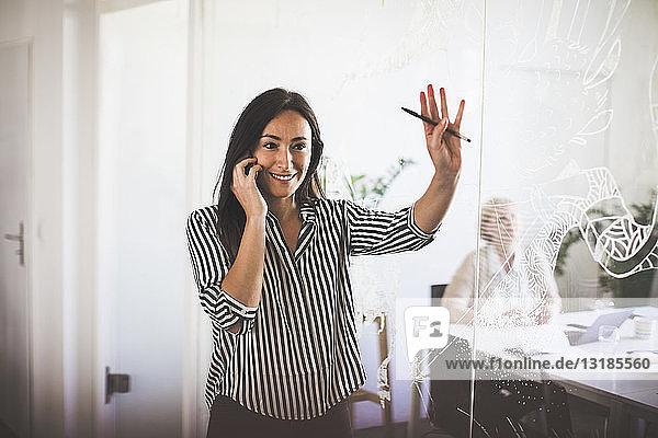 Lächelnde  kreative Geschäftsfrau gestikuliert beim Telefonieren mit dem Handy im Sitzungssaal