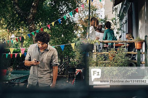 Junger Mann benutzt Mobiltelefon  während er im Hinterhof steht