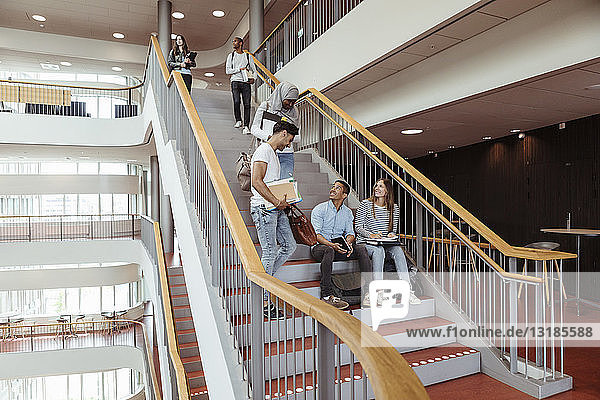 Glückliche multiethnische Freunde unterhalten sich auf den Stufen des High-School-Campus