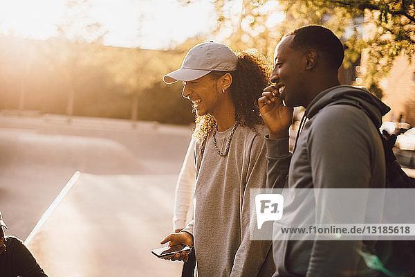 Glückliche Freunde im Gespräch mit einem Mann im Skateboard-Park