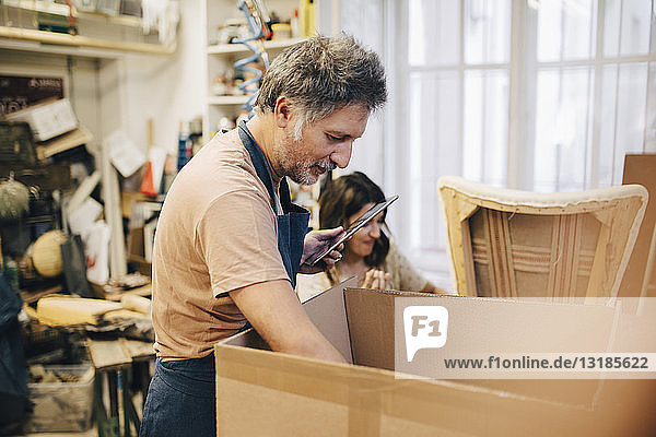 Male craftsperson holding digital tablet while looking in cardboard box at workshop