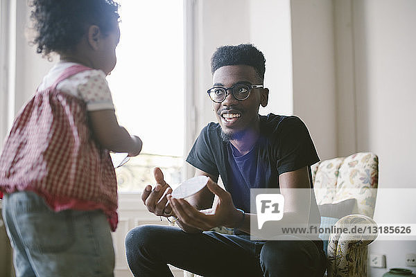 Young man playing with daughter at home