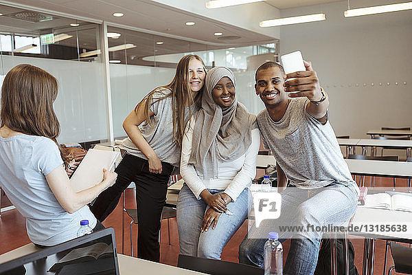 Lächelnder Mann nimmt sich mit Freundinnen am Smartphone im Klassenzimmer ein