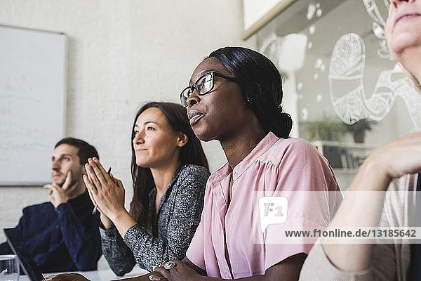 Kreative Geschäftsleute  die während einer Sitzung im Sitzungssaal sitzen und zuhören
