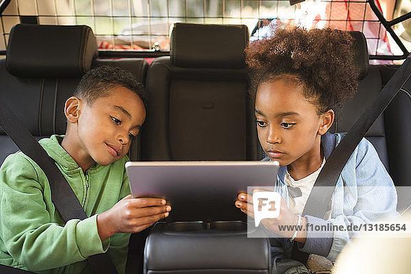 Geschwister teilen sich ein digitales Tablet  während sie in einem Elektroauto sitzen