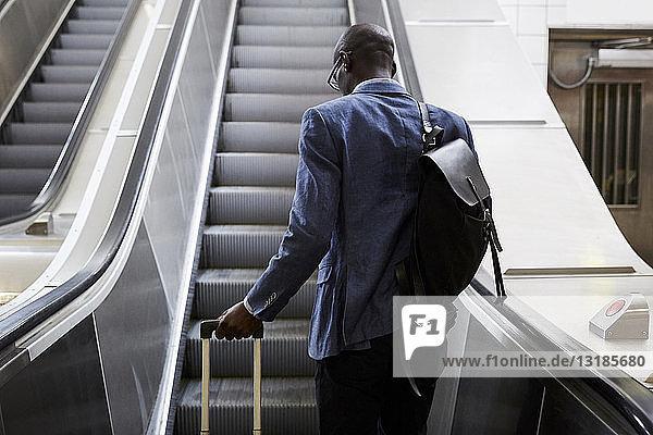 Rückansicht eines Geschäftsmannes  der mit Gepäck auf der Rolltreppe in der U-Bahn-Station steht