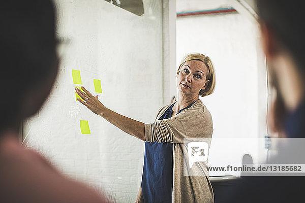 Kreative Geschäftsfrau erklärt Kollegen bei Bürobesprechung über Klebezettel auf Glas