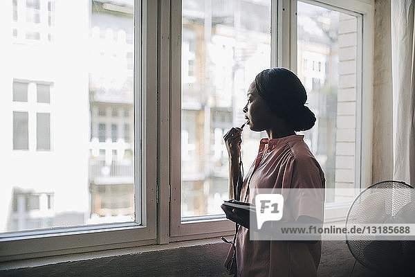 Junge Geschäftsfrau spricht durch Kopfhörer  während sie in einem kreativen Büro am Fenster steht