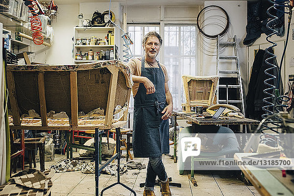 Porträt eines reifen männlichen Handwerkers neben einem unvollständigen Sofa in einer Polsterwerkstatt