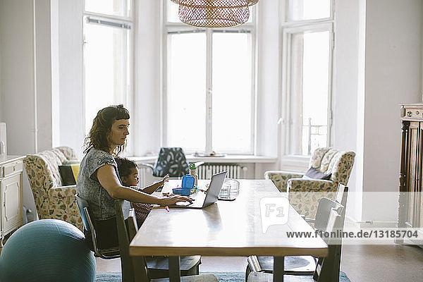 Mutter benutzt Laptop  während sie mit dem kleinen Mädchen am Tisch im Haus sitzt