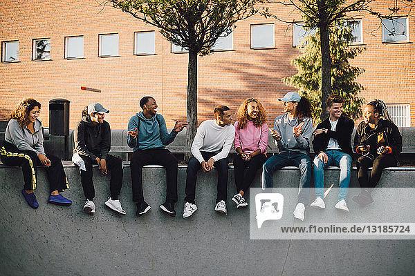 Multi-ethnische Freunde in voller Länge im Skateboard-Park sitzend