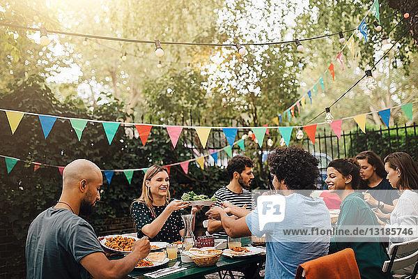 Junge männliche und weibliche Freunde genießen das Abendessen während der Gartenparty